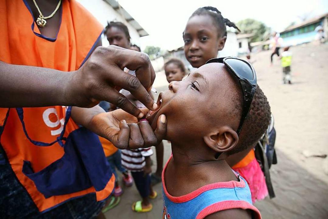Ein liberianischer Junge erhält in der...Old Road Tropfen des Polio-Impfstoffs.    Foto: Ahmed Jallanzo (dpa)