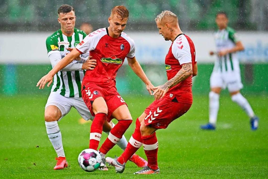 Florian Kamberi (l) vom FC St.Gallen im Zweikampf mit Philipp Lienhart (M).  | Foto: Gian Ehrenzeller (dpa)
