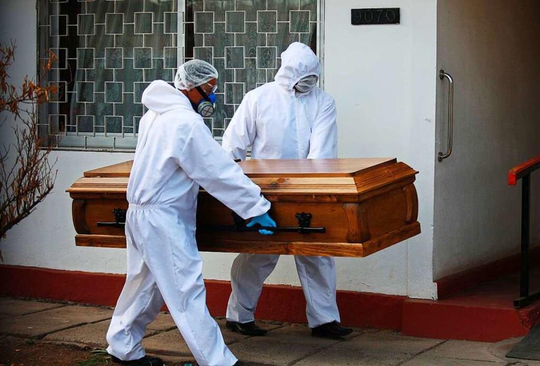 Arbeiter betreten ein Pflegeheim in Sa...onavirus gestorbenen Person abzuholen.  | Foto: Jose Francisco Zuñiga (dpa)