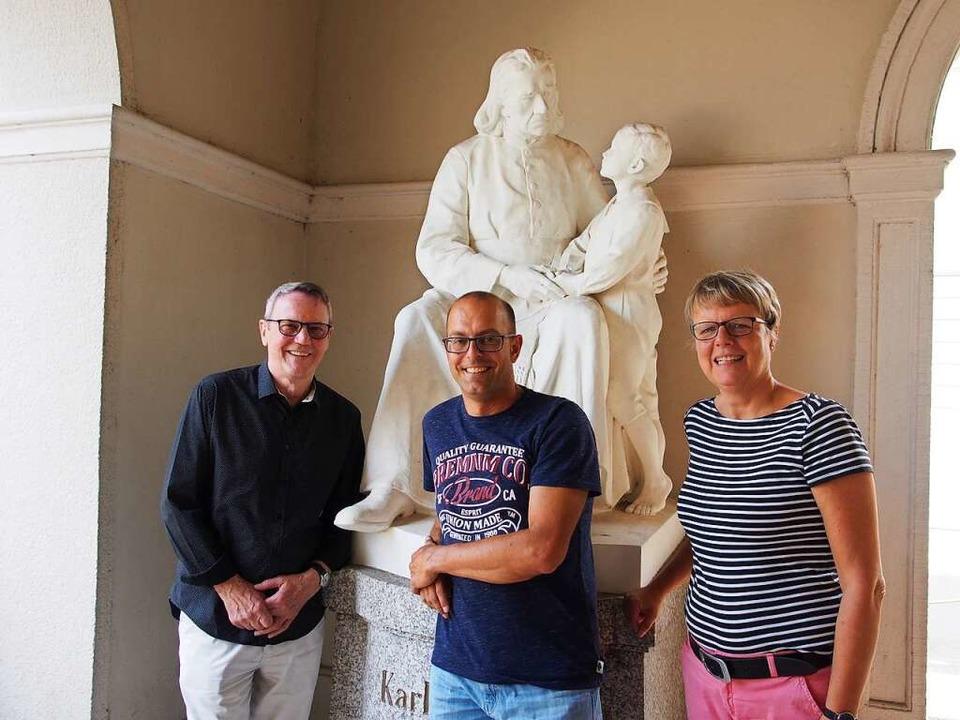 Ferdinand Müller (von links), Thomas M...git Hehl an der Statue von Karl Rolfus  | Foto: Boris Burkhardt