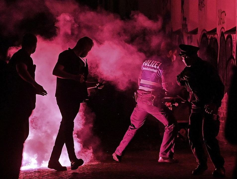 Polizisten fliehen am Samstag bei einer Demo in Leipzig vor Pyrotechnik.  | Foto: Hendrik Schmidt (dpa)