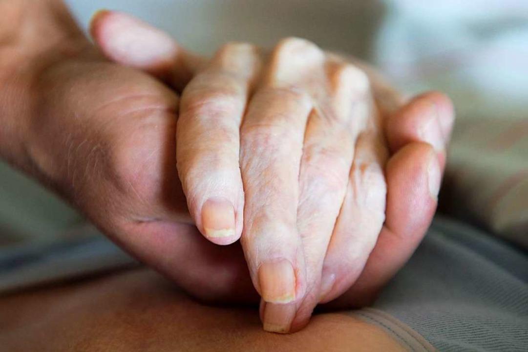 Ein Altenpfleger hält in einem Pflegeheim die Hand einer Frau.  | Foto: Sebastian Kahnert (dpa)