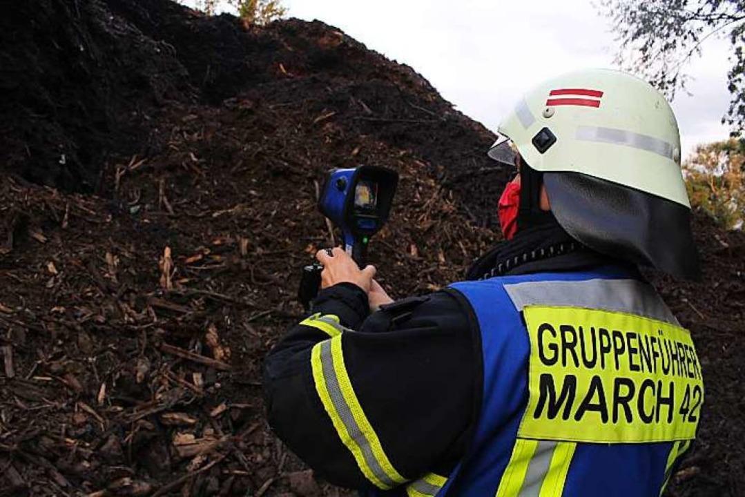 Mit einer Wärmebildkamera misst ein Fe... die Hitze in dem Holz- und Erdhaufen.  | Foto: Feuerwehr March