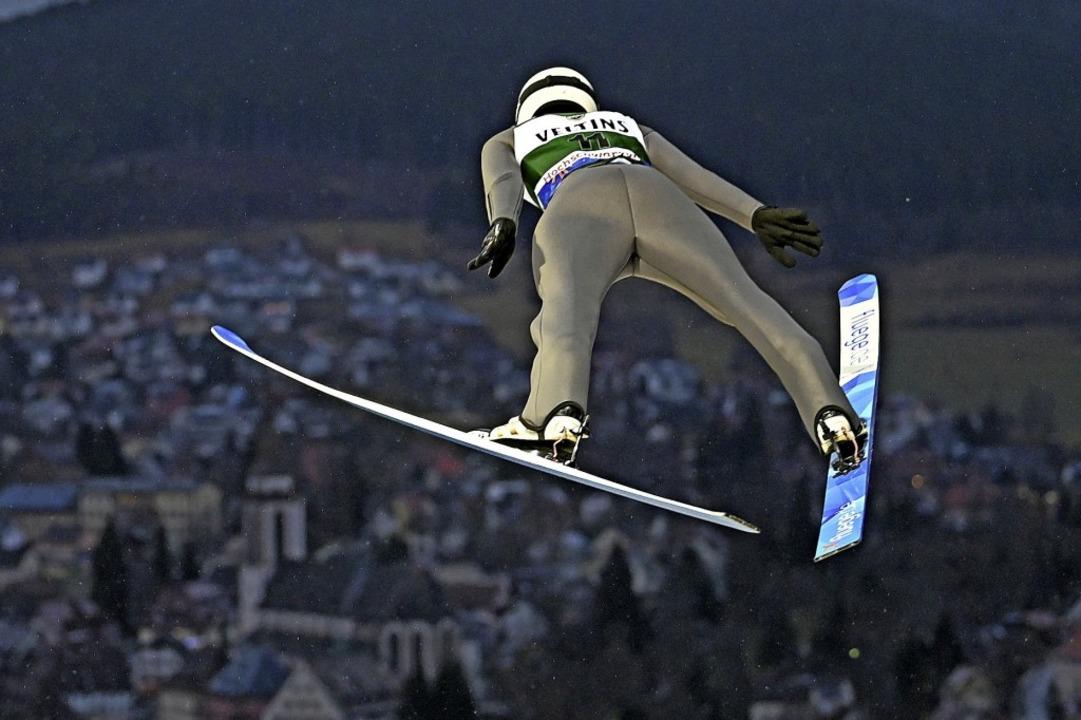 Skispringer sind nachtaktiv. Luca Roth...ne ein Menschenmeer im Zuschauerrund.   | Foto: Patrick Seeger (dpa)