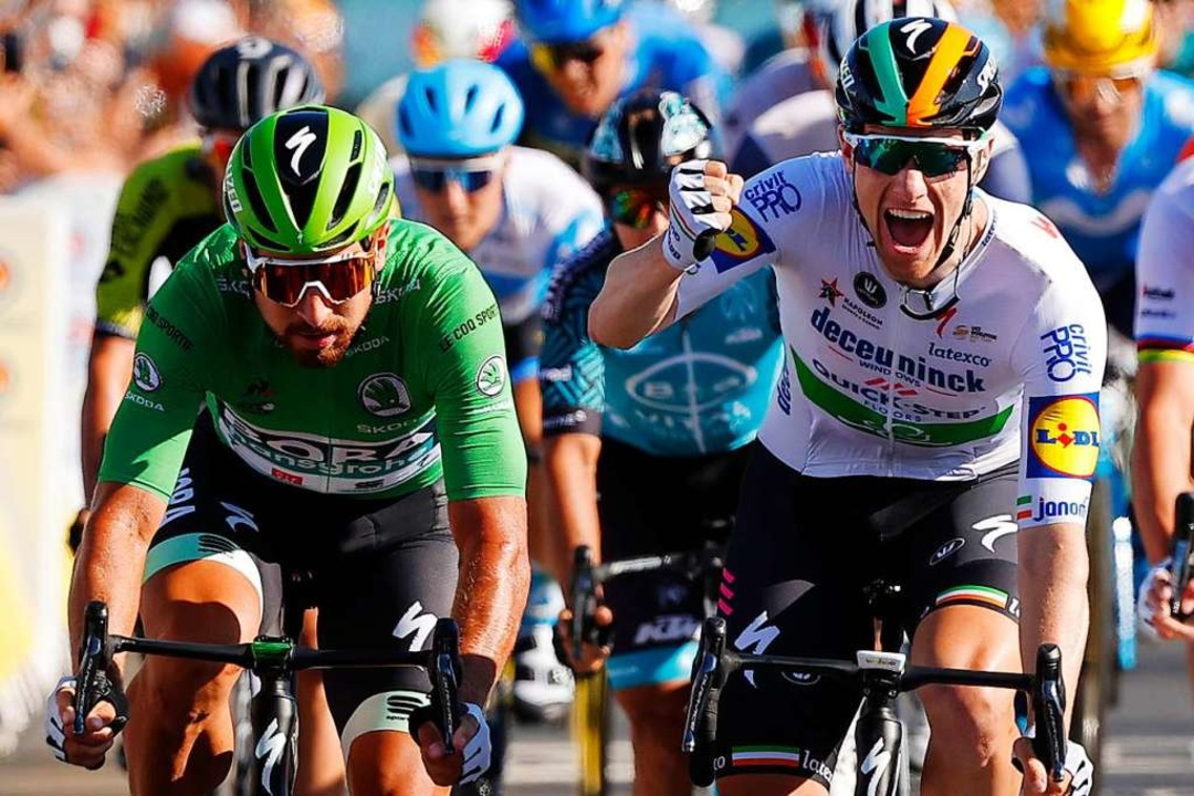 Sam Bennett überfährt als Sieger der z... die Ziellinie bei der Tour de France.  | Foto: - (dpa)