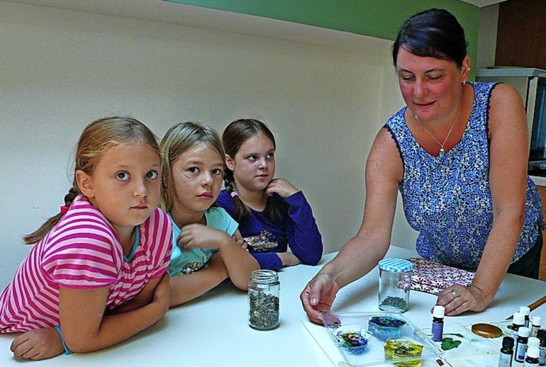 Tina Müller gießt mit Kindern Seife.  | Foto: Nina Herrmann