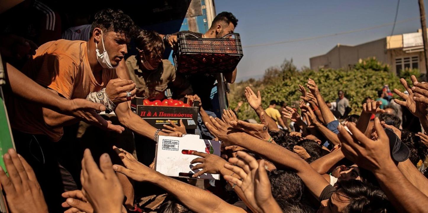 Helfer verteilen am Donnerstag Lebensm...denen Flüchtlinge aus dem Lager Moria.  | Foto: ANGELOS TZORTZINIS (AFP)