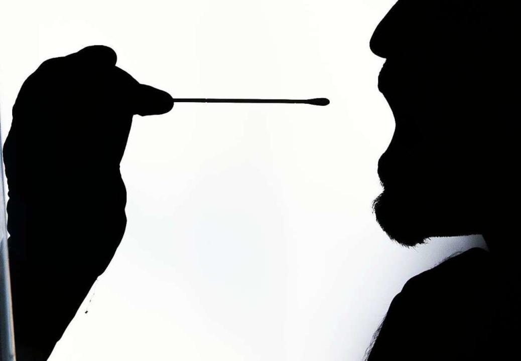 Ein Mann wird per Stäbchen in einem Testzentrum auf das Corona-Virus getestet.  | Foto: Lino Mirgeler (dpa)