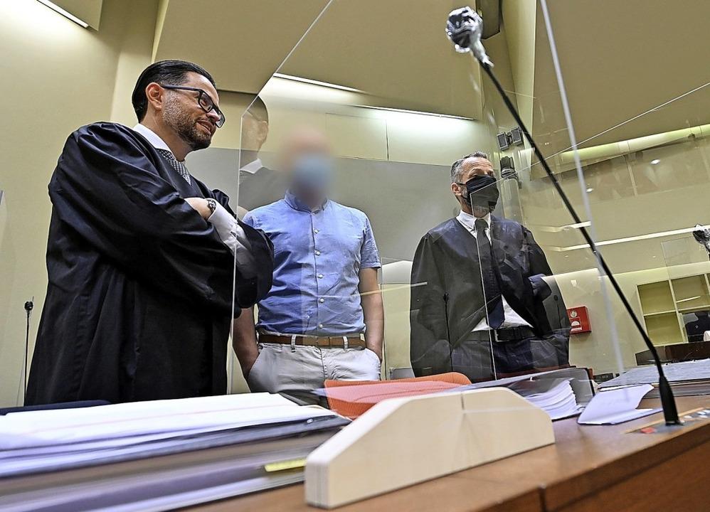 Der Angeklagte (Mitte) steht beimBegi...en ihn  mit seinen Anwälten zusammen.   | Foto: Peter Kneffel (dpa)