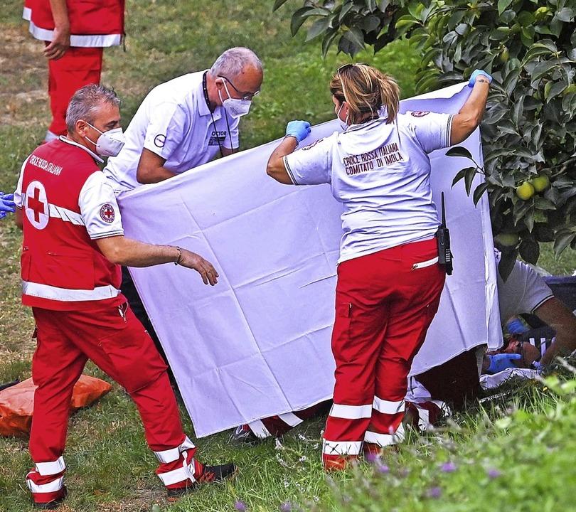 Helfer kümmern sich um die gestürzte Titelverteidigerin Chloé Dygert  | Foto: MARCO BERTORELLO (AFP)
