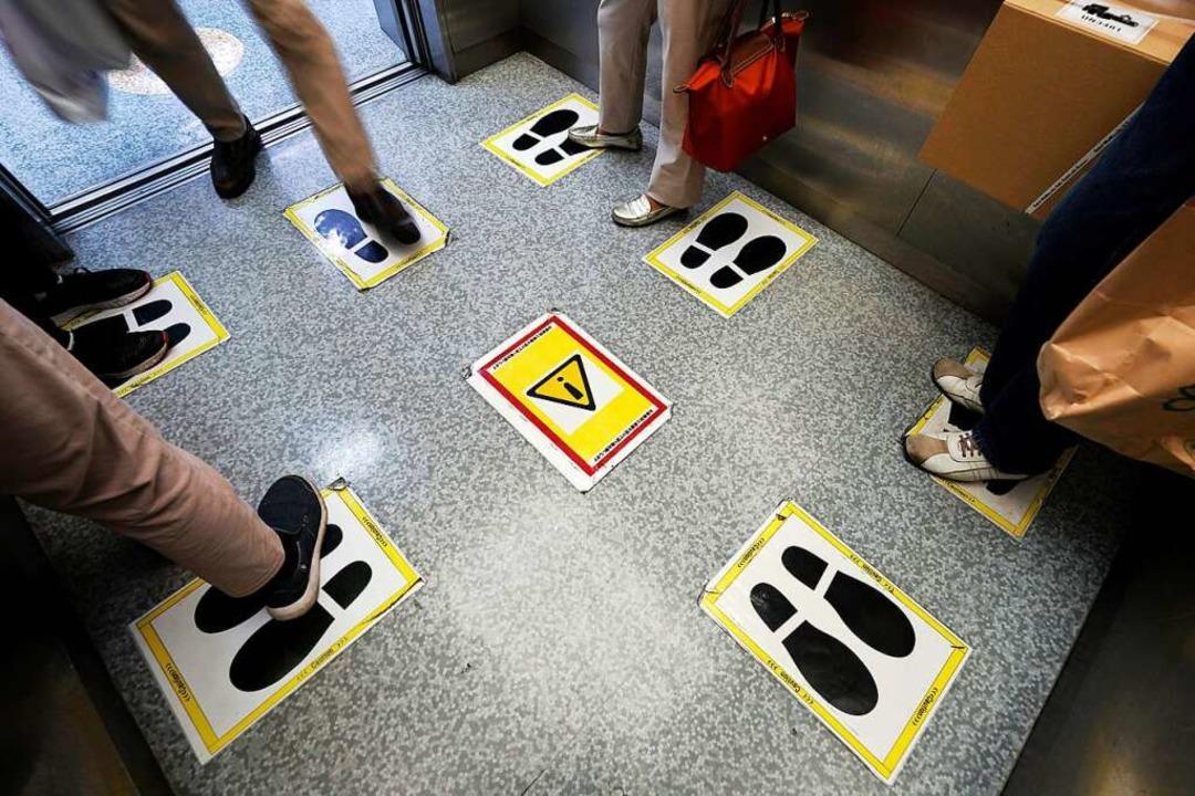In einem Fahrstuhl markieren Aufkleber... Abstände während der Corona-Pandemie.    Foto: Eugene Hoshiko (dpa)