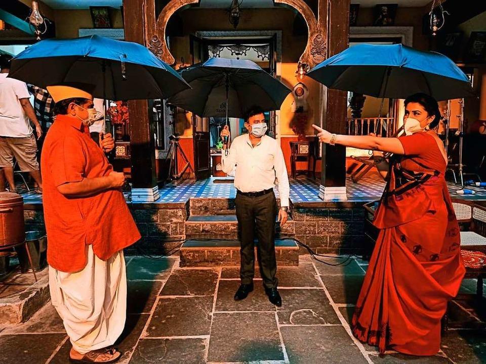 Mit aufgespannten Regenschirmen proben...enügend Abstand voneinander zu halten.  | Foto: - (dpa)