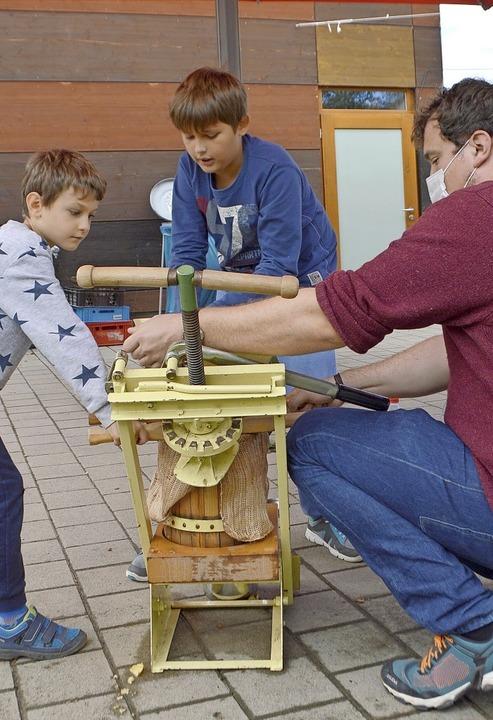 Malte Lindemann hilft Lucas (links) und Bastian beim Mosten an der Trotte.    Foto: Horatio Gollin
