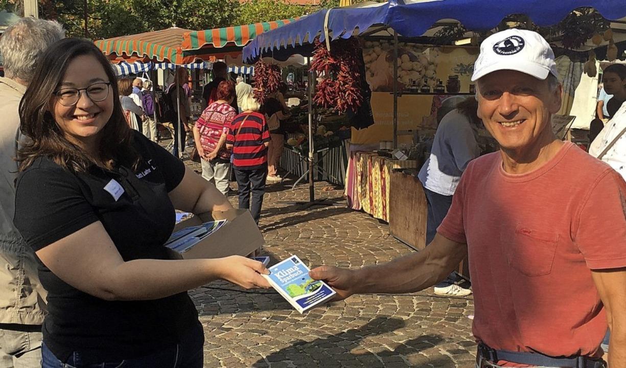 Klimaschutzmanagerin Madeleine Krol üb...Lahrer Wochenmarkt ein Klimasparbuch.   | Foto: Stadt Lahr
