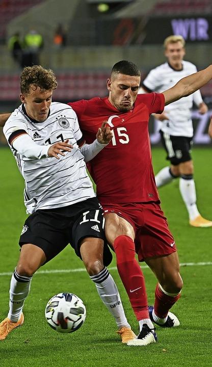 Luca Waldschmidt (links) schirmt gegen Merih Demiral den Ball ab.    Foto: Federico Gambarini (dpa)