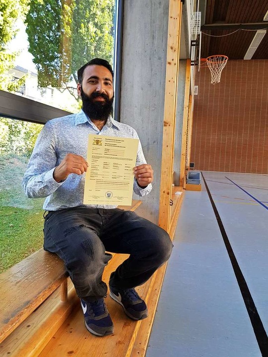 Atif Aman zeigt sein Abschlusszeugnis in der Schulturnhalle.   | Foto: Schule