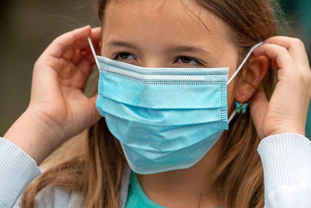 Ein Mädchen zieht einen Mund-Nasenschutz an.  | Foto: Boris Roessler (dpa)