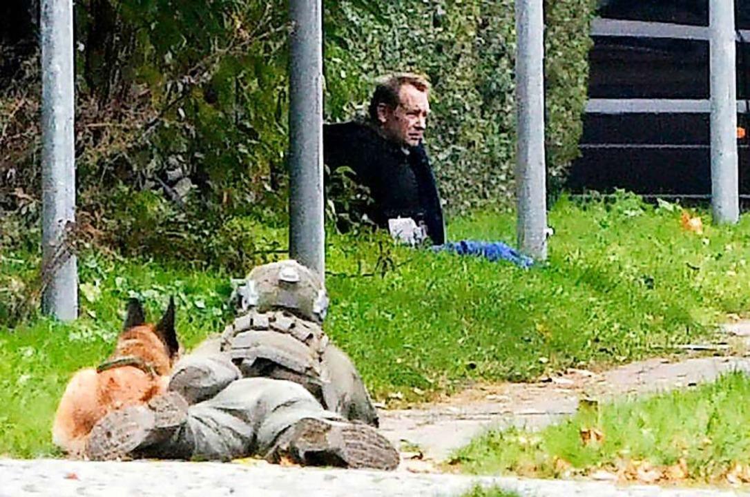 Ein Polizist liegt neben einem Polizei...einem Straßenrand auf dem Boden sitzt.  | Foto: Nils Meilvang (dpa)