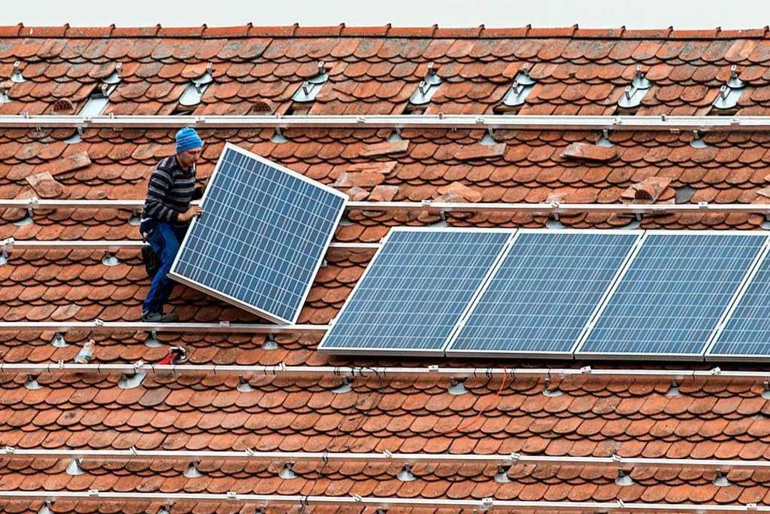 Ein Arbeiter installiert eine Photovol...n soll es in Ehrenkirchen mehr geben.   | Foto: Armin Weigel