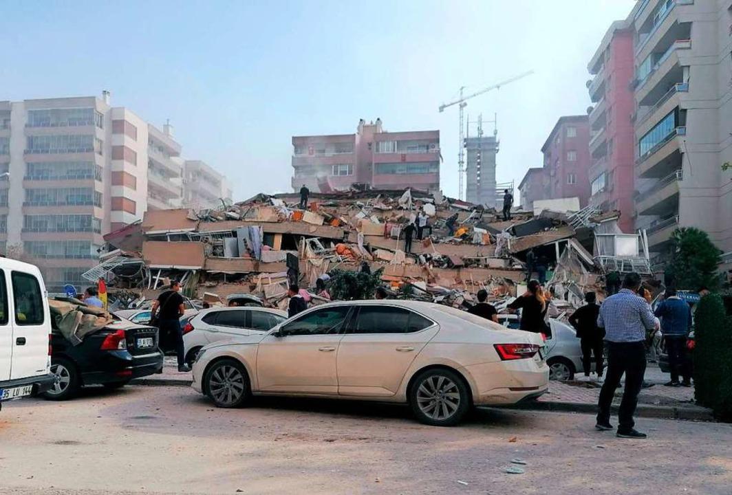 In Izmir stehen Menschen vor einem zusammengestürzten Gebäude.  | Foto: Uncredited (dpa)