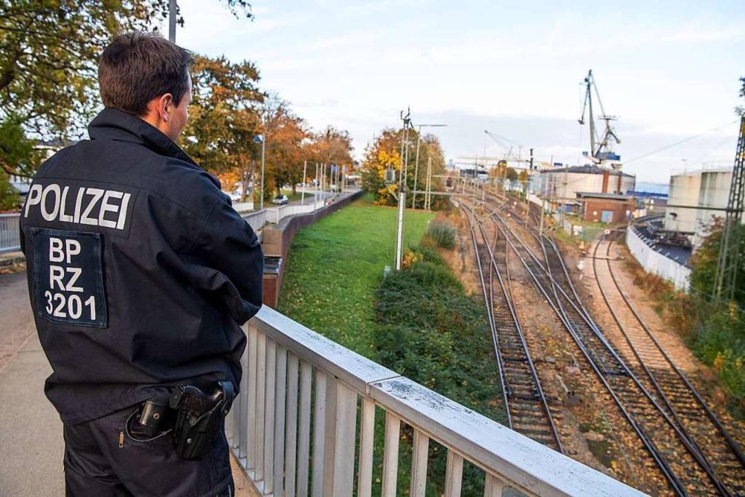 Ein Bundespolizist steht an den Gleise...den Castor-Transport behindern wollen.  | Foto: Sina Schuldt (dpa)