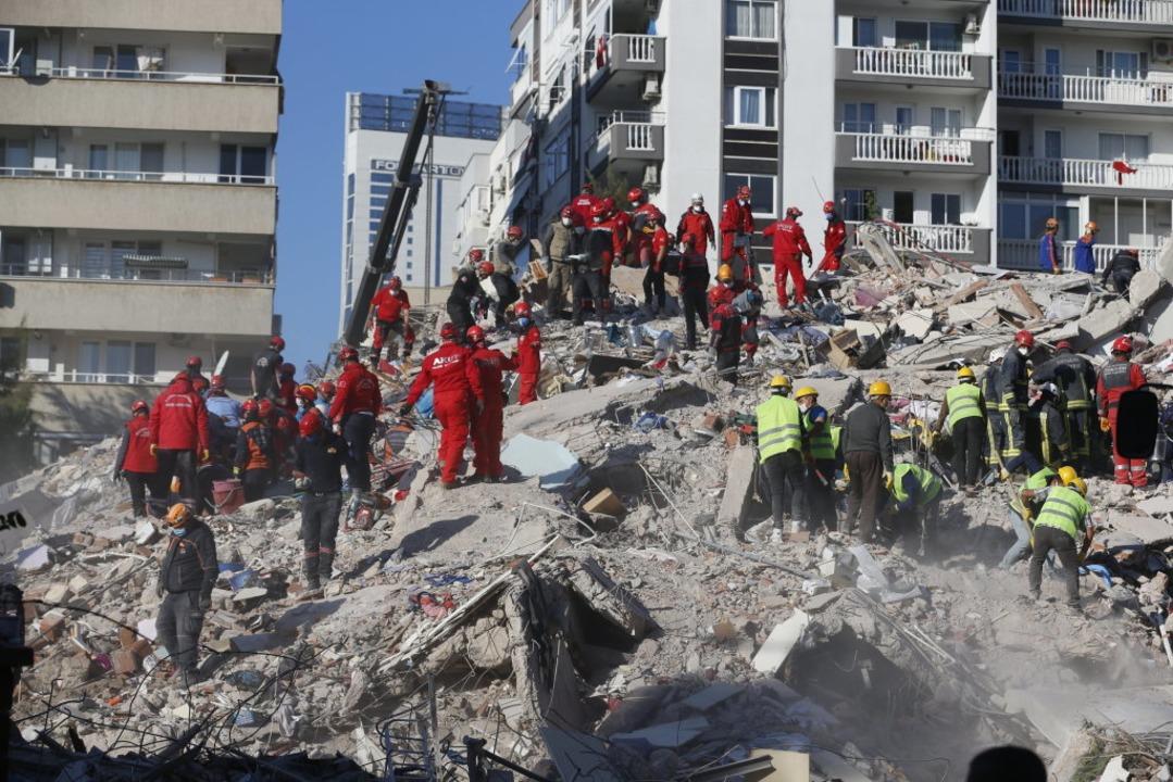 Rettungskräfte in Izmir suchen nach Üb...Trümmern eines eingestürzten Gebäudes.  | Foto: Darko Bandic (dpa)
