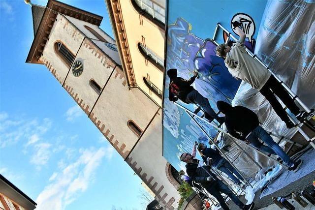 Jugendliche und ein Künstler verschönern Sicherungswand bei der Lörracher Stadtkirche
