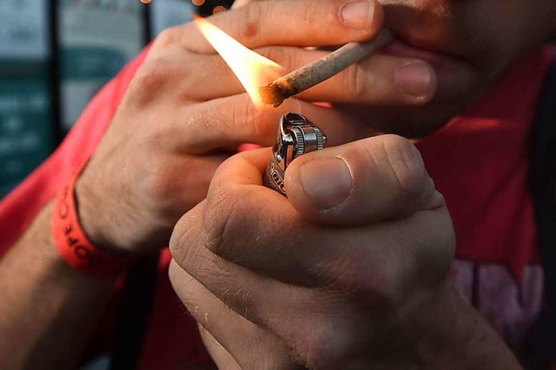 Ein Mann zündet sich einen Joint an.  | Foto: JOSH EDELSON (AFP)
