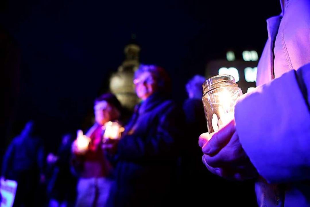 Mit Kerzen in den Händen und ausreiche...ärften Corona-Maßnahmen protestieren.   | Foto: Robert Michael (dpa)