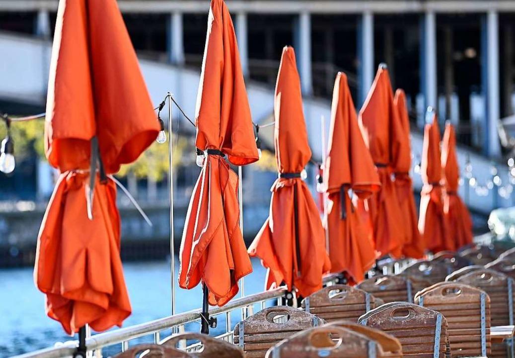 Zusammengeklappte Sonnenschirme und leere Stühle    Foto: Britta Pedersen (dpa)