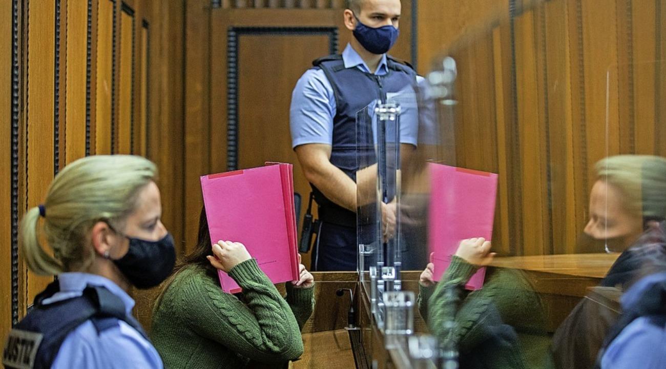 Die angeklagte  Kita-Erzieherin versteckt sich hinter einem Ordner.    Foto: Rolf Vennenbernd (dpa)