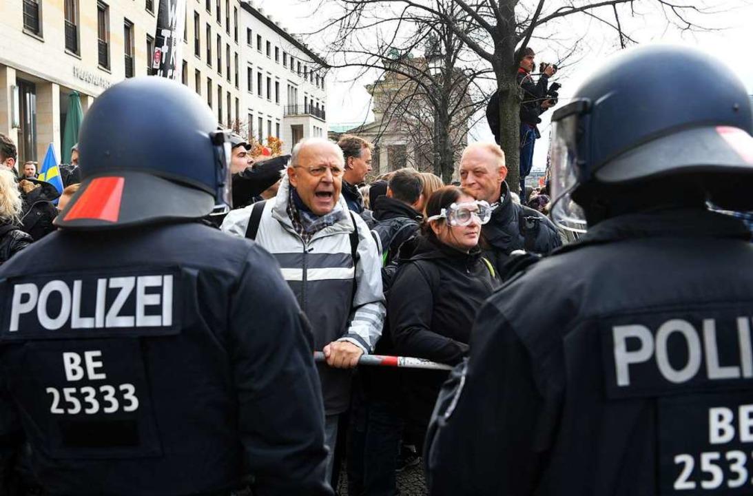 Teilnehmer einer Demonstration gegen d...r und dem Reichstagsgebäude gegenüber.  | Foto: Paul Zinken (dpa)