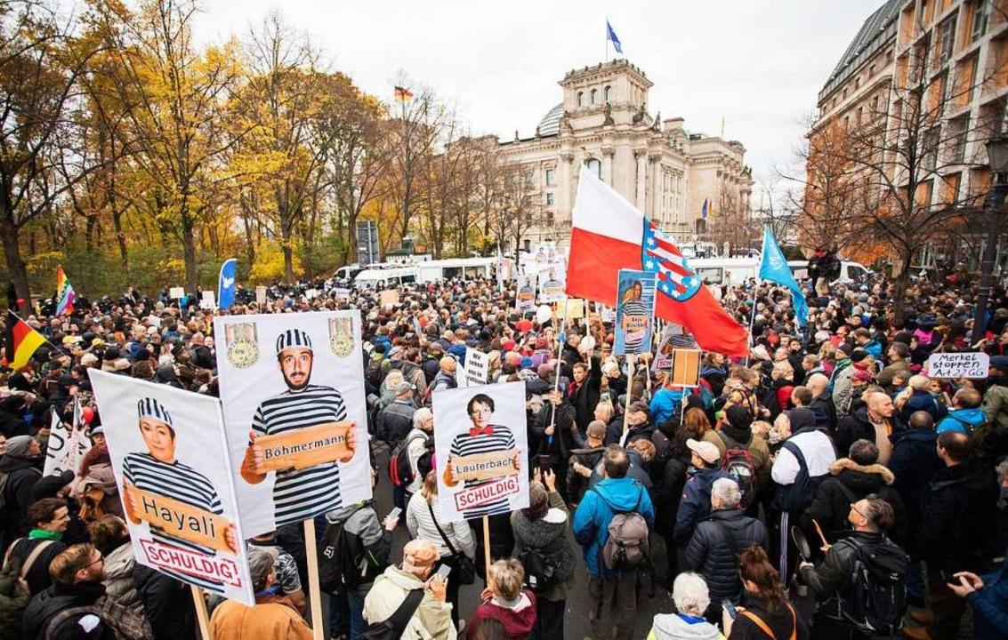 "Teilnehmer einer Demonstration gegen d...t dem Schriftzug ""schuldig"".  | Foto: Christoph Soeder (dpa)"