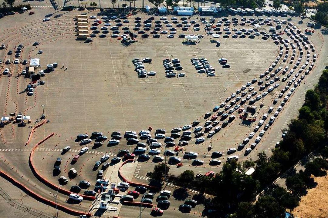 Autofahrer warten in ihren Fahrzeugen ..., um dort einen Corona-Test zu machen.  | Foto: Ringo H.W. Chiu (dpa)