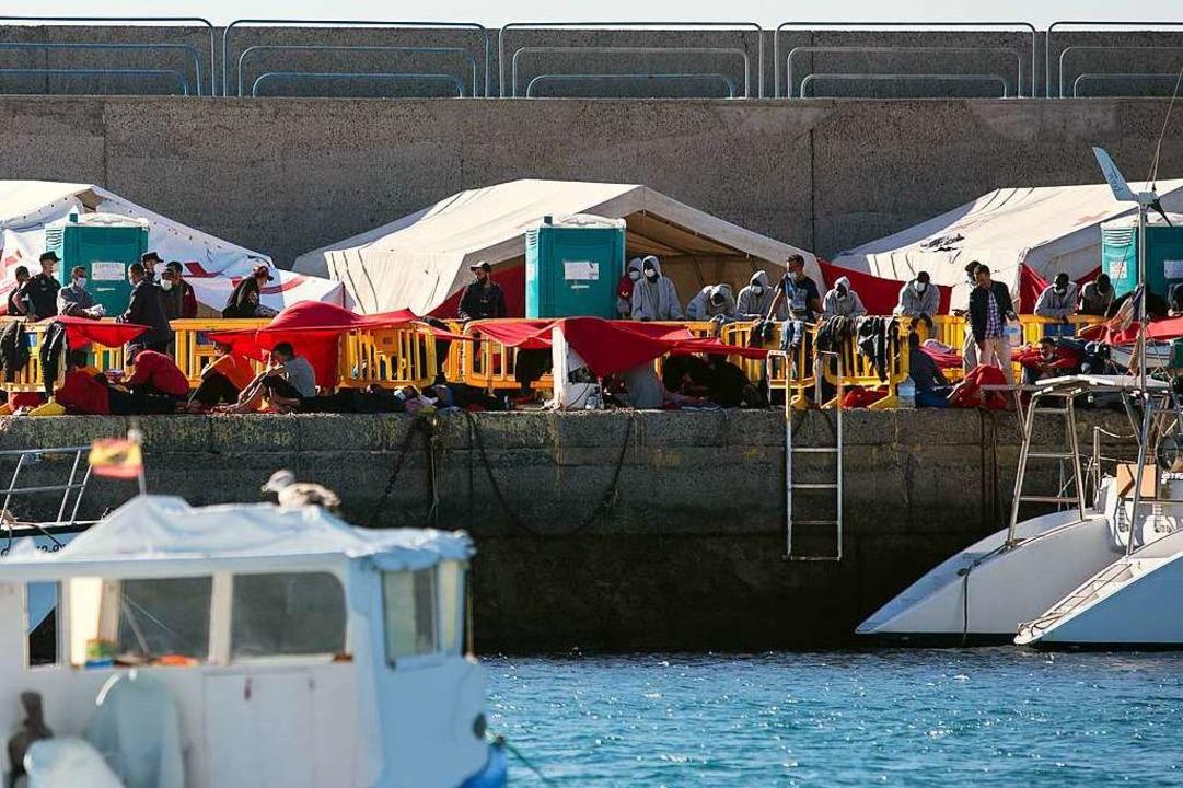 Migranten stehen an der Mole der Hafen...ineguín im Südwesten von Gran Canaria.  | Foto: Manuel Navarro (dpa)