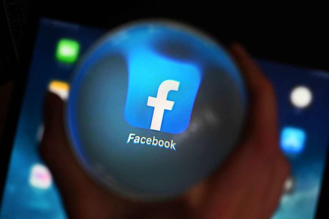 Eine Person schaut durch eine Glaskugel auf einem Tablet auf die Facebook App.  | Foto: Uli Deck (dpa)