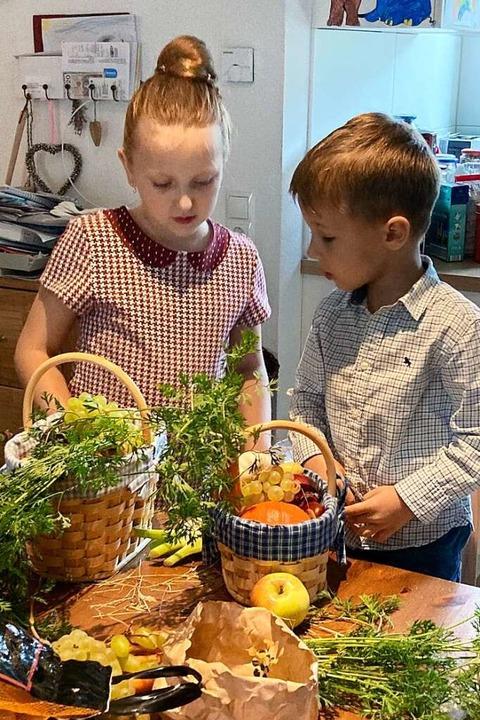 Louisa und Raphael Bogdan beim Körbchen füllen vor dem Gottesdienst  | Foto: Dora Schöls