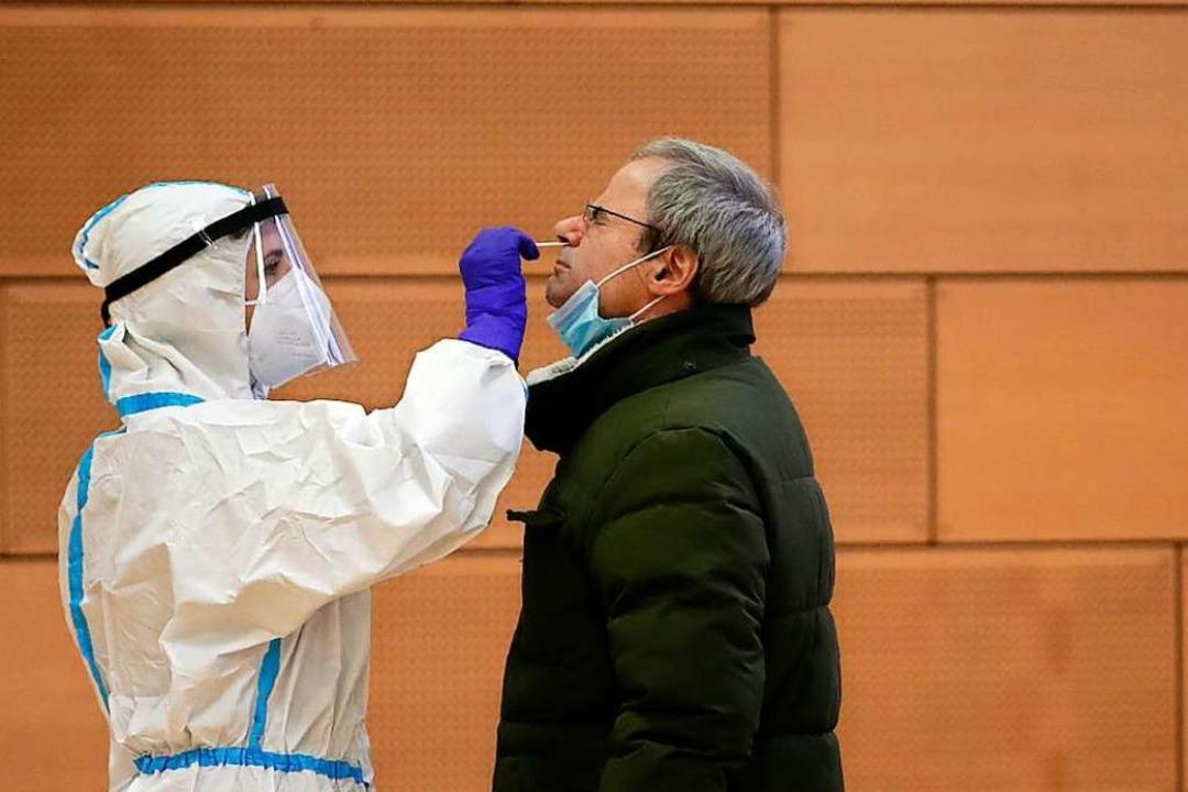 Ein medizinischer Mitarbeiter in Schut...einen Corona-Test an einem Mann durch.  | Foto: Antonio Calanni (dpa)