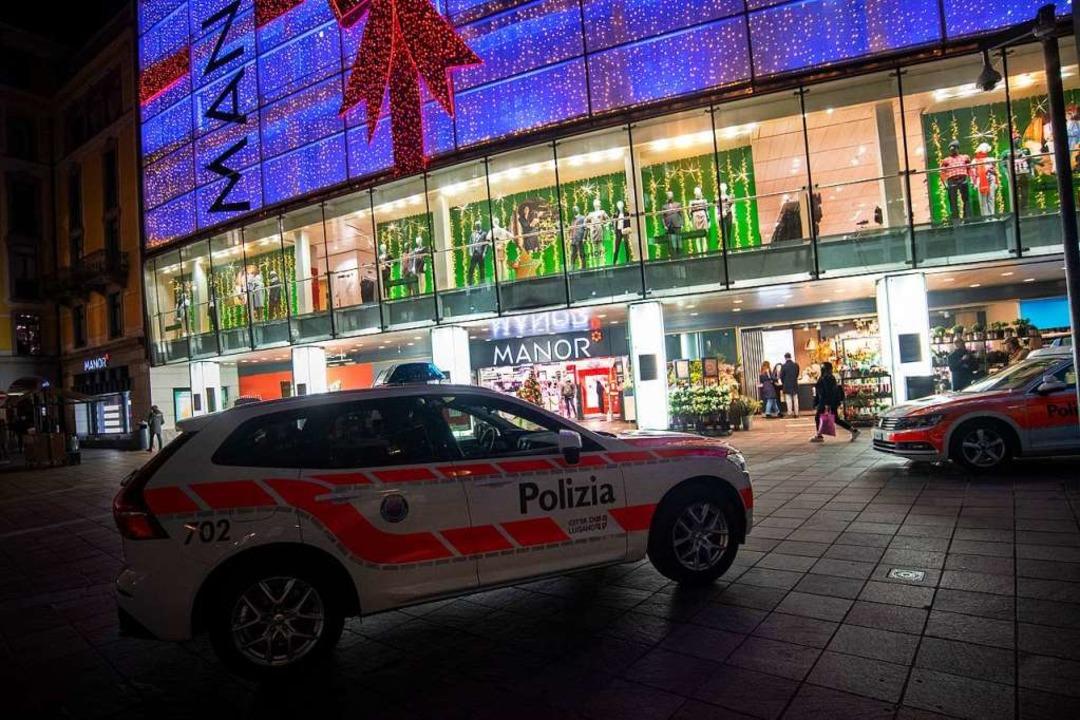 Polizeifahrzeuge stehen vor dem Kaufha...ante im schweizerischen Kanton Tessin.  | Foto: Pablo Gianinazzi (dpa)