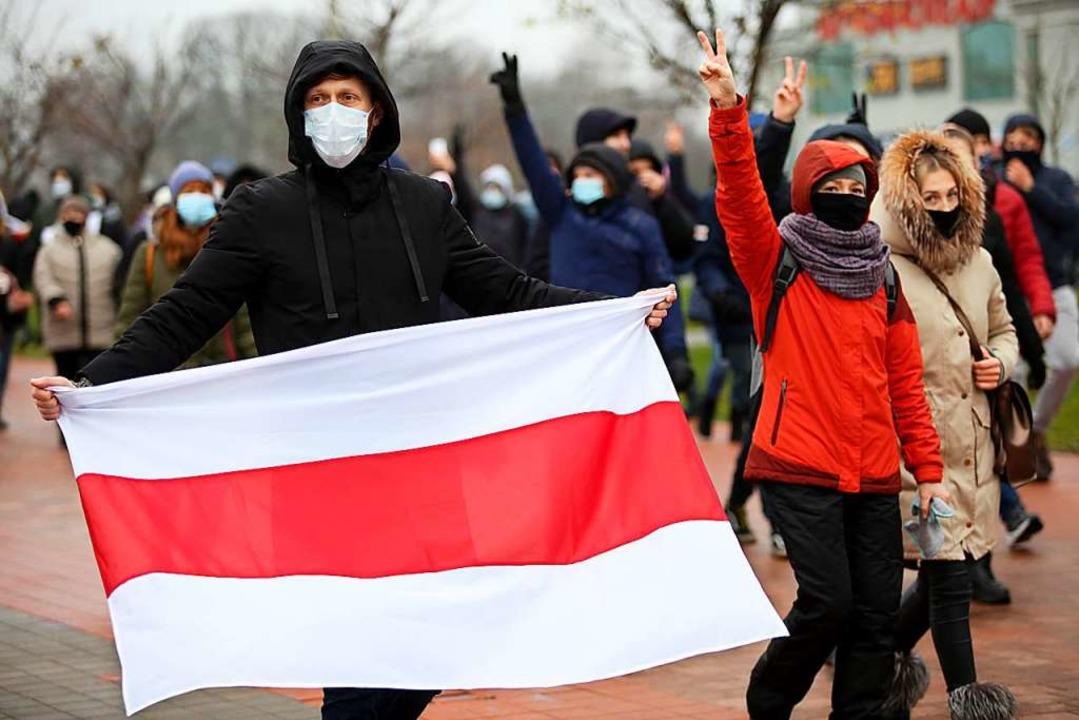 Ein Demonstrant hält bei einem Protest...gen Lukaschenko friedlich protestiert.  | Foto: - (dpa)