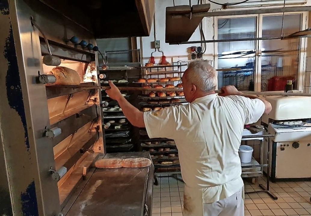 Helmuth Bender holt das fertige Brot aus dem Ofen.     Foto: Anja Hoffmann