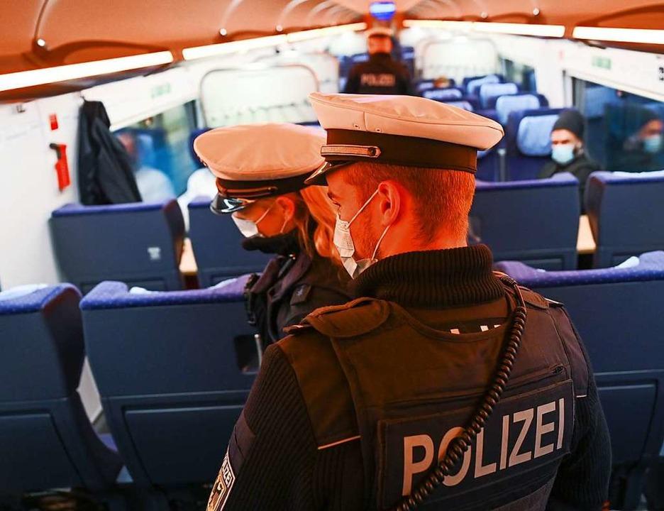 Polizisten der Bundespolizei kontrolli... das Tragen von Mund-Nase-Bedeckungen.  | Foto: Arne Dedert (dpa)