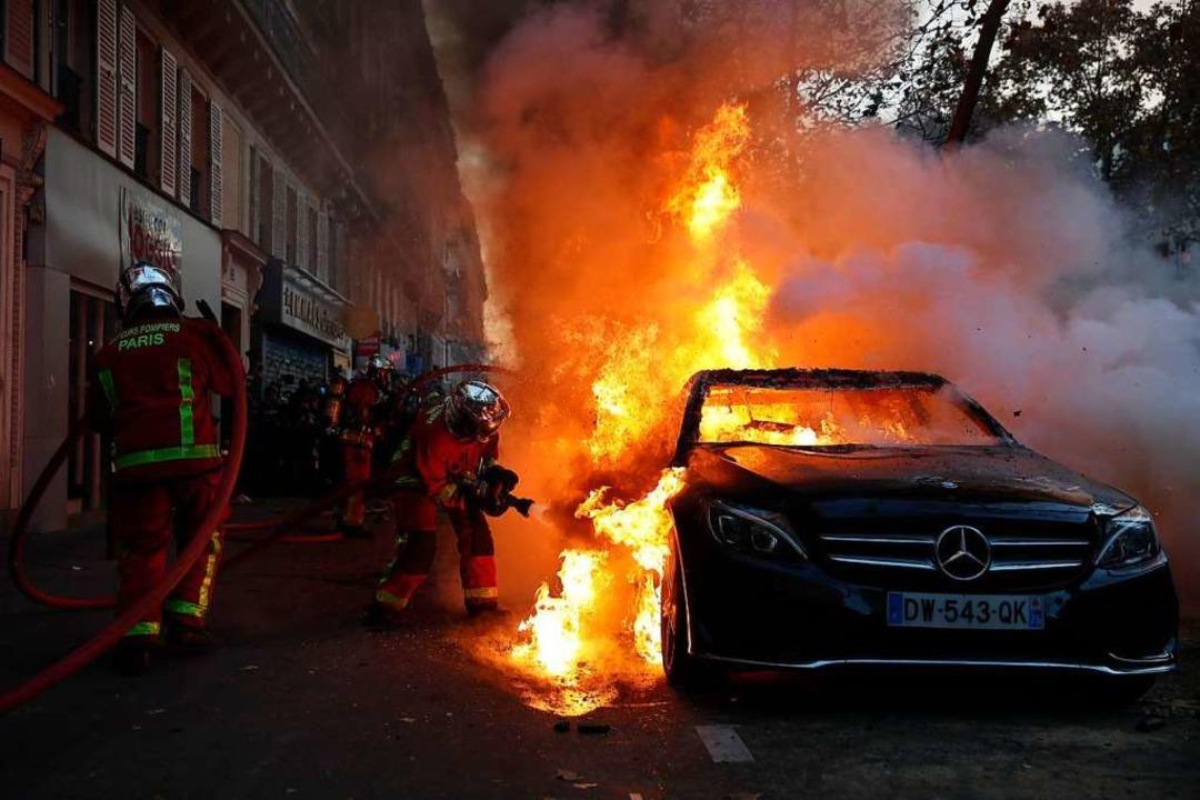 Feuerwehrkräfte löschen ein  brennende...icherheitsgesetz eskalierte die Gewalt    Foto: Francois Mori (dpa)