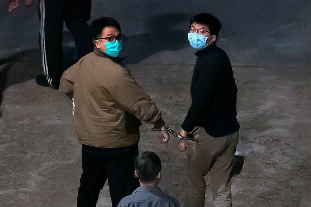 Die Aktivisten Ivan Lam (links) und Jo...r gekettet, am Mittwoch ins Gefängnis.  | Foto: Kin Cheung (dpa)
