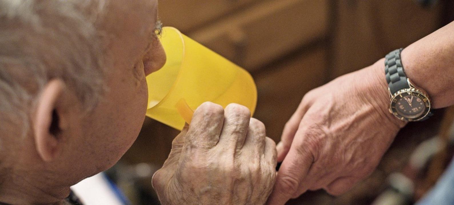 Eine ambulante Pflegerin hilft einem alten Mann bei der Tabletteneinnahme.    Foto: Jana Bauch (dpa)