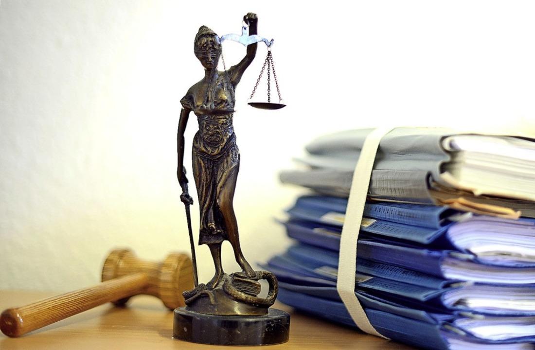 Justitia, Aktenstapel und Holzhammer im Büro eines Richters    Foto: Volker Hartmann (dpa)