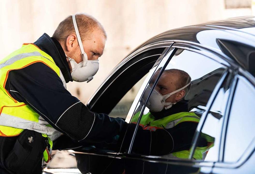 Ein Bundespolizist überprüft Autofahre...e nicht gegen Corona-Regeln verstoßen.  | Foto: Patrick Seeger (dpa)
