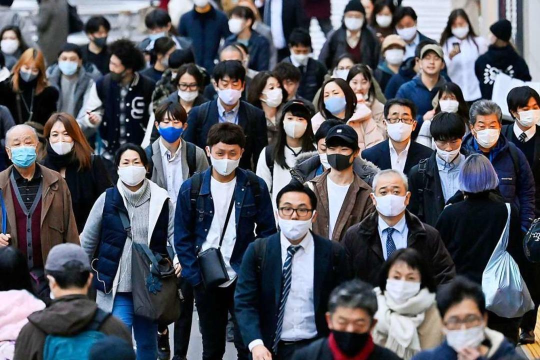 Passanten mit Mund-Nasen-Schutz in Tikio    Foto: Yohei Nishimura (dpa)