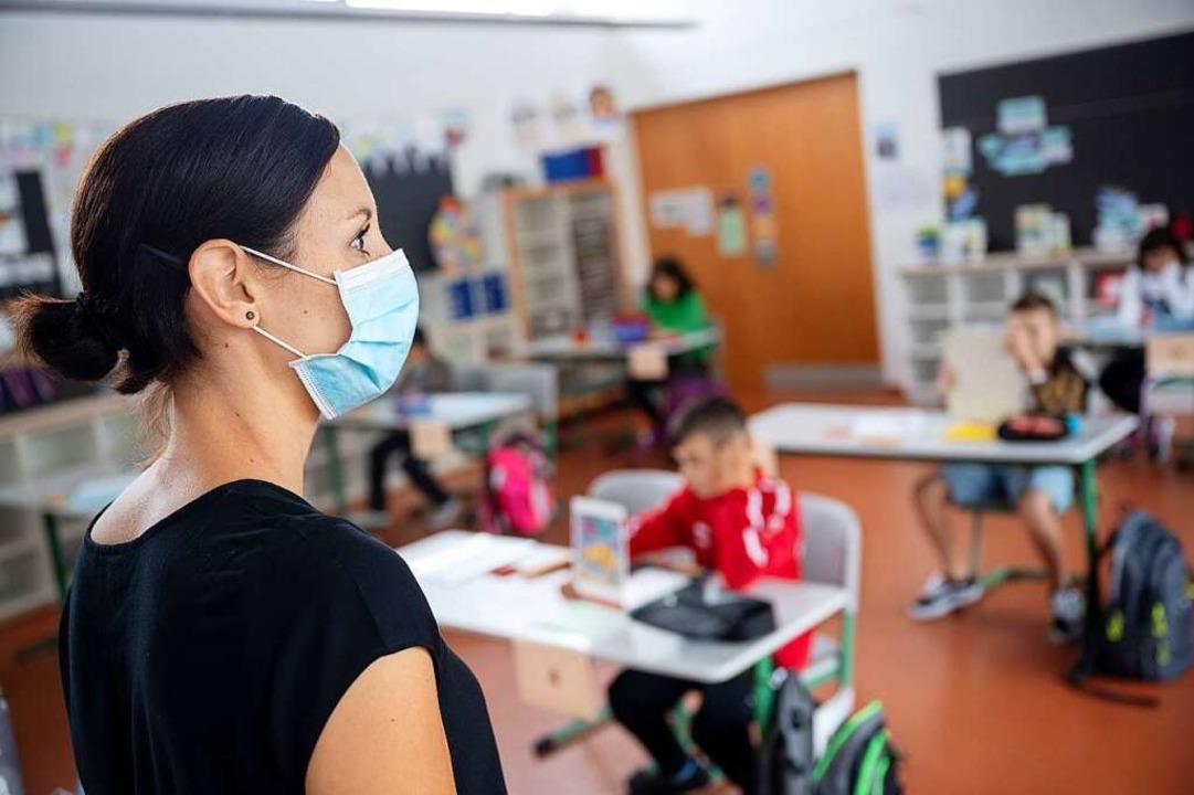 Eine Lehrerin mit Maske steht vor einer Grundschulklasse (Symbolbild).  | Foto: Sebastian Gollnow (dpa)