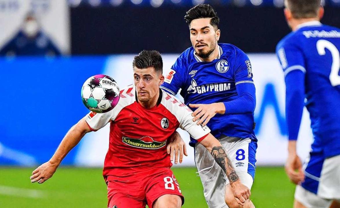 Freiburgs Baptiste Santamaria (l) und Schalkes Suat Serdar in Aktion.  | Foto: Martin Meissner (dpa)